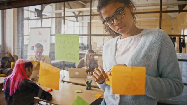 vídeos y material grabado en eventos de stock de joven señora afroamericana mirando la pared de vidrio y pegando pegatina con idea en ella, cámara lenta - pegajoso