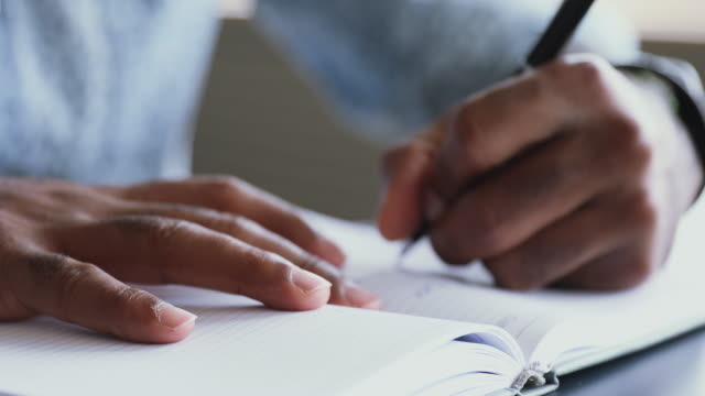 vídeos de stock, filmes e b-roll de jovem estudante afro-americano escrevendo notas em papel. - escrever