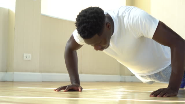 Young African American man doing push-up on the floor. Determined male fit sportsman at fitness gym center Young African American man doing push-up on the floor. Determined male fit sportsman at fitness gym center push ups stock videos & royalty-free footage