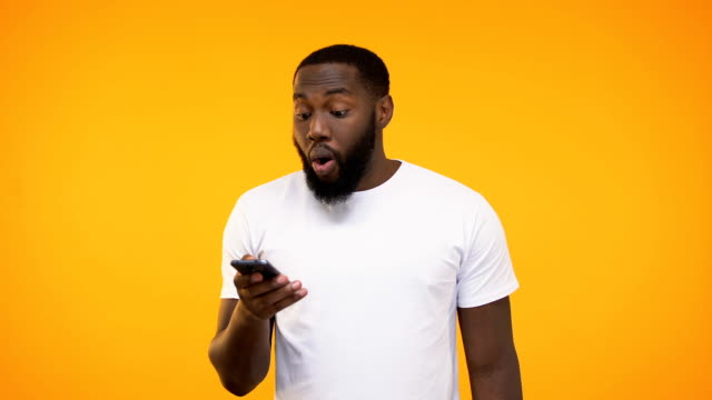 young african american man holding cellphone, job approving message, application - sorpresa video stock e b–roll