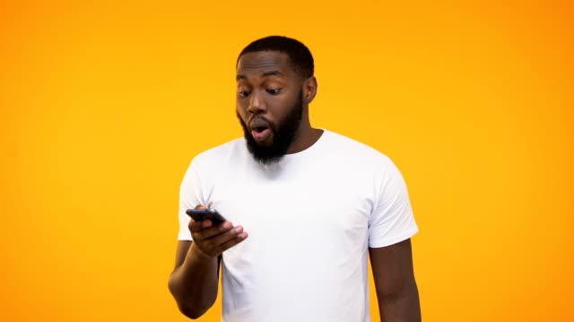 핸드폰을 들고 젊은 아프리카계 미국인 남자, 메시지, 응용 프로그램을 승인 하는 작업 - surprise 스톡 비디오 및 b-롤 화면