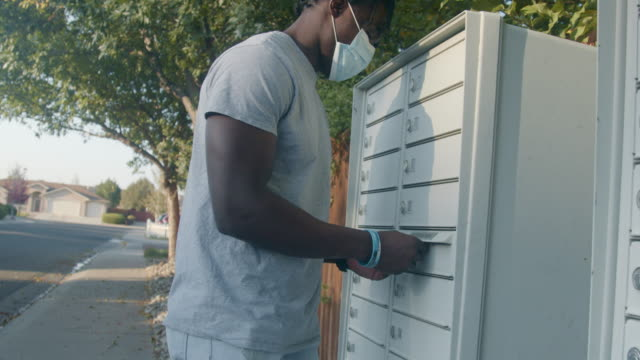 Young African American Man in his twenties wearing a covid-19 mask carrying a ballot to mail to vote in an election while social distancing