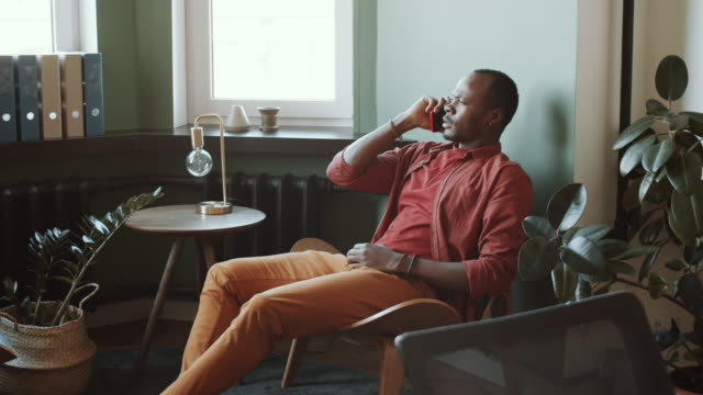 Young African American Man Talking on Mobile Phone in Office Breakout Area