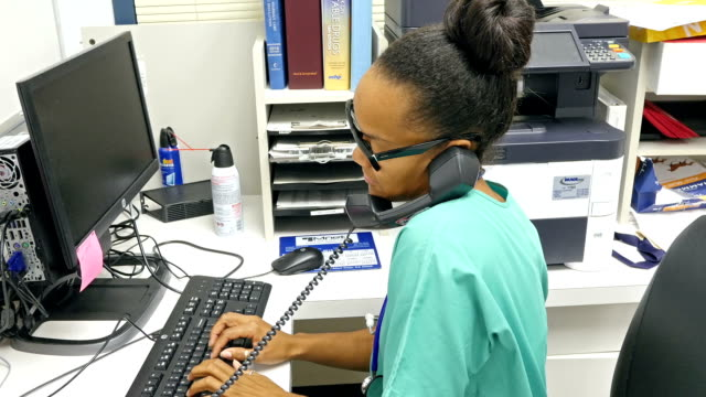 Young African American nurse at nurses' station answering phone Young African American nurse is in nurses station inputting information from tablet to desktop computer.  While she is typing, the phone rings and she answers it while continuing to type.  She has brief conversation and then hangs up the phone. nurse stock videos & royalty-free footage