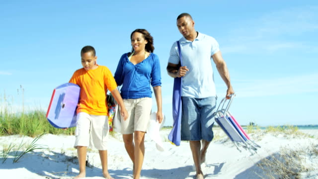 Young African American parents and son with surfboard