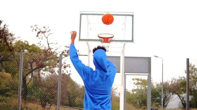 Young african american playing basketball on the street and throwing a ball to the basket unsuccessfully. Slowmotion shot Young african american playing basketball on the street and throwing a ball to the basket unsuccessfully. Slowmotion shot. scoring a goal stock videos & royalty-free footage