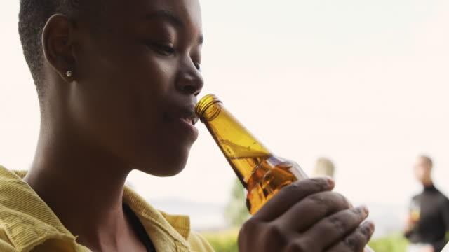 ung afroamerikansk kvinna som dricker en öl på ett tak - alkohol bildbanksvideor och videomaterial från bakom kulisserna