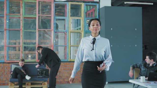 若いアフリカ系アメリカ人の女性が聴衆に入り、フリップチャートに来て、同僚を歓迎します。プレゼンテーション。クリエイティブなオフィスインテリア。コワーキングスタートアップチ� ビデオ