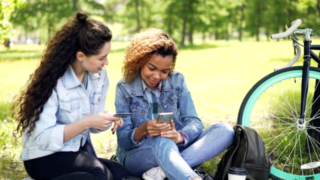 Young African American woman is shopping online making payment with smartphone while her friend in holding credit card, girls are sitting on lawn in park in summer.