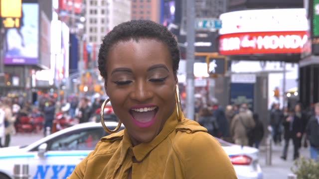 junge afrikanische amerikanische frau lachen und lächeln beim sitzen in der mitte ein sehr belebten times square new york city - ohrring stock-videos und b-roll-filmmaterial