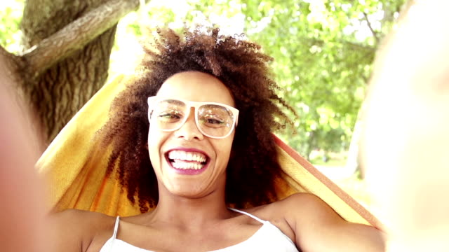 Young african american woman lying in hammock laughing video