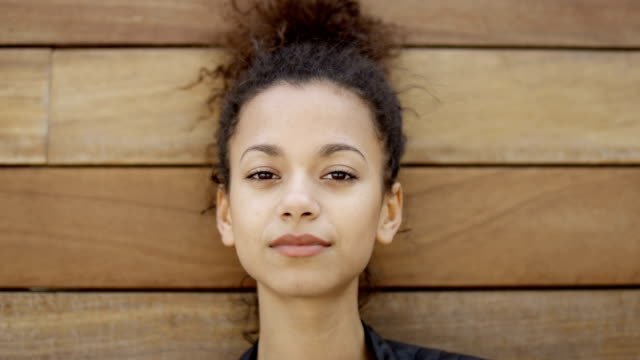 Young african american woman posing outdoors over wooden background.