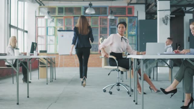A young African American woman rides a chair through the office to her colleague at a nearby desk, after a young employee in a business suit passes by. Co-working. Office interior in loft style video