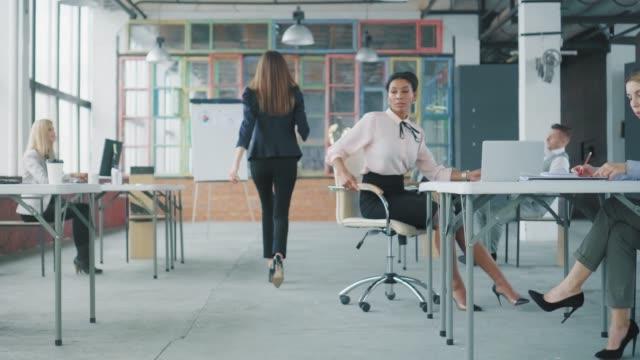 Eine junge Afroamerikanerin fährt über einen Stuhl durch das Büro zu ihrem Kollegen an einem nahegelegenen Schreibtisch, nachdem eine junge Angestellte in einem Business-Anzug vorbeigezogen ist. Co-Working. Büroausstattung im Loft-Stil – Video