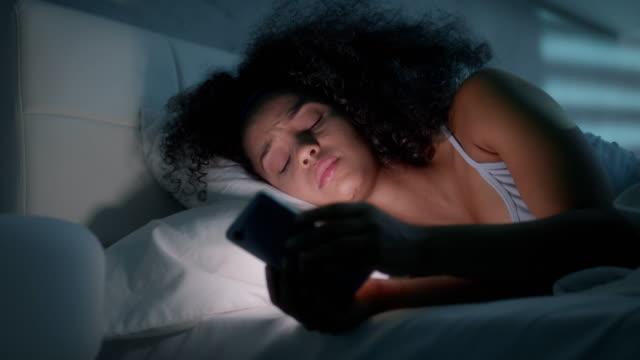 yatakta smartphone ile genç afro-amerikan kadın manifatura - sms göndermek stok videoları ve detay görüntü çekimi