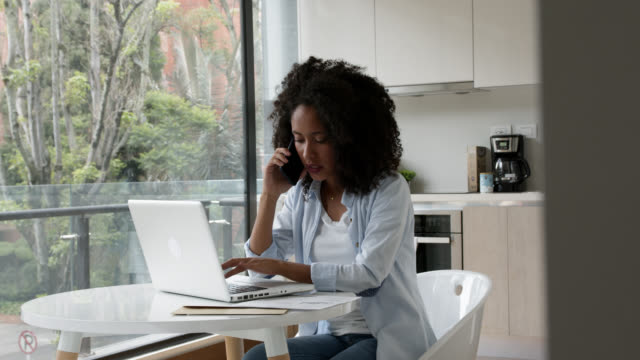 Young African American woman working from home and talking on the phone while typing on computer