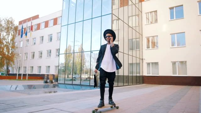 Young african black hipster businessman riding longboard and talking on phone video