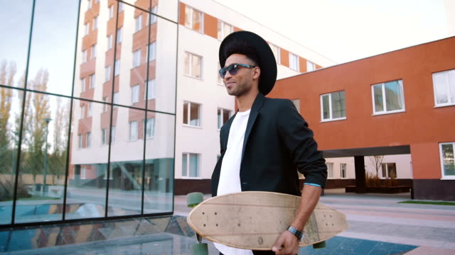 Young african black hipster businessman walking with longboard on urban background video