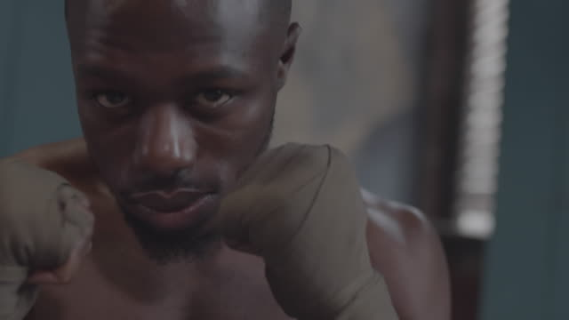 Young African Boxer Posing with Clenched Fists to Face in Locker Room