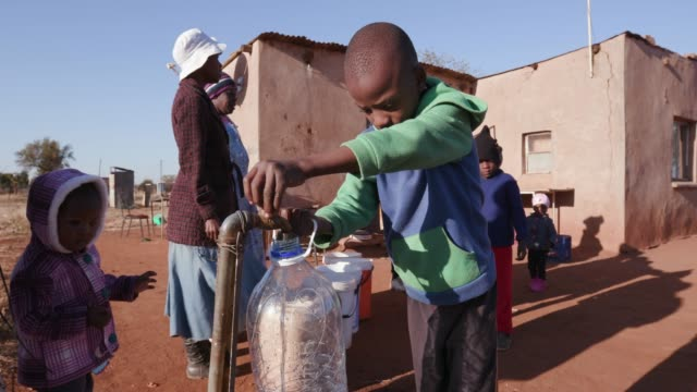 young african boy collecting water from a tap while woman line up to collect water in plastic containers due to severe drought in south africa - bambine africa video stock e b–roll