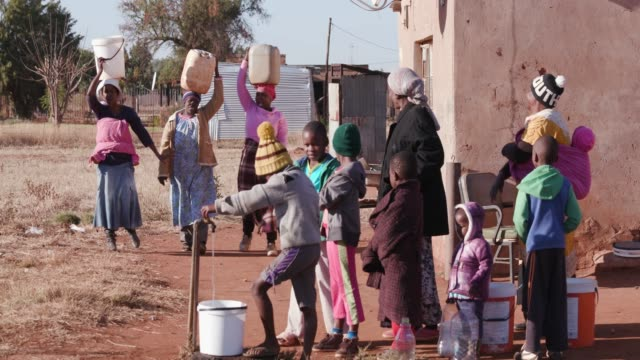 Young african boys drinking water from a tap while woman line up to collect water in plastic containers due to severe drought in South Africa Young african boys drinking water from a tap while woman line up to collect water in plastic containers due to severe drought in South Africa poverty stock videos & royalty-free footage