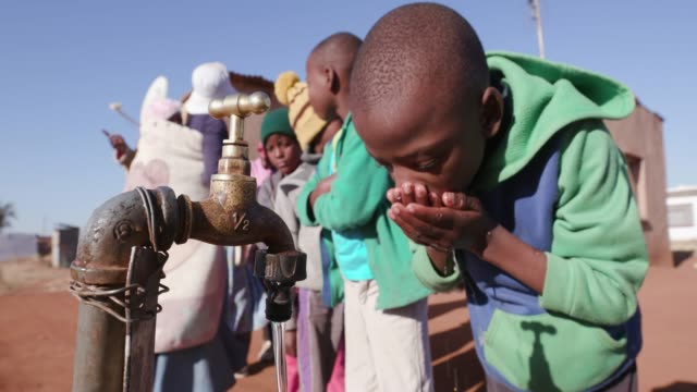 young african boys drinking water from a tap while woman line up to collect water in plastic containers due to severe drought in south africa - republika południowej afryki filmów i materiałów b-roll