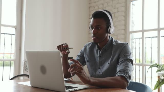 unga afrikanska affärsman bära hörlurar videosamtal på laptop - videor med headphones bildbanksvideor och videomaterial från bakom kulisserna