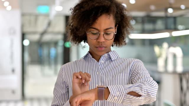 vídeos de stock, filmes e b-roll de jovem empresária africana usando smartwatch - punho