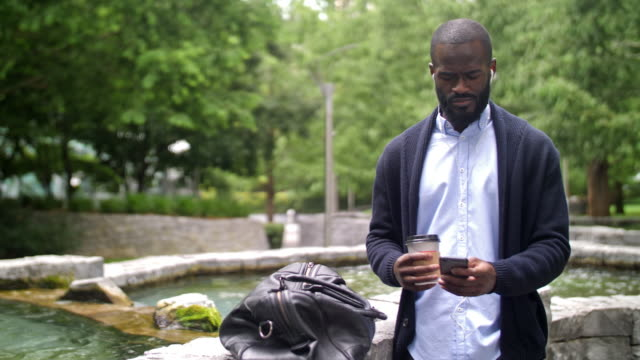 Young African city professional in London 4K color footage of a British city professional of African descent having a hands-free phone call in London. bluetooth stock videos & royalty-free footage