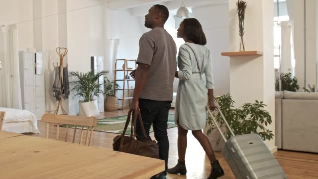 Young African couple entering holiday rental accommodation Couple with luggages walk into large stylish loft apartment, hug and loving their holiday vacation lodgings hotel stock videos & royalty-free footage