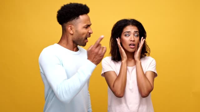 Young african couple having a conflict, woman is closing her ears with hands isolated over yellow background video