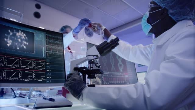 vidéos et rushes de jeune microbiologiste africain d'ethnicité étudiant le coronavirus - vaccin covid