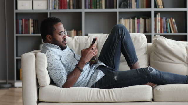 Young african guy using phone relax on sofa at home