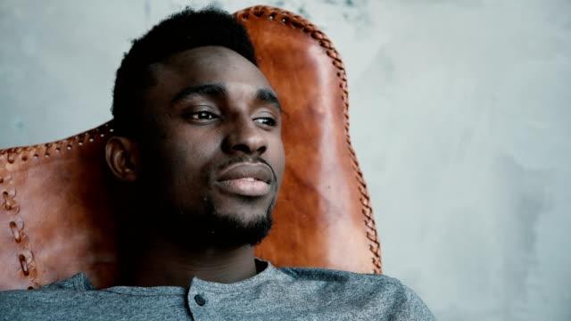 Un varón africano joven sentado en la silla, mirando hacia la distancia y pensando en algo. Hombre de aspecto pensativo - vídeo