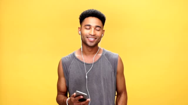 Young african man chatting and listening music over yellow background. video