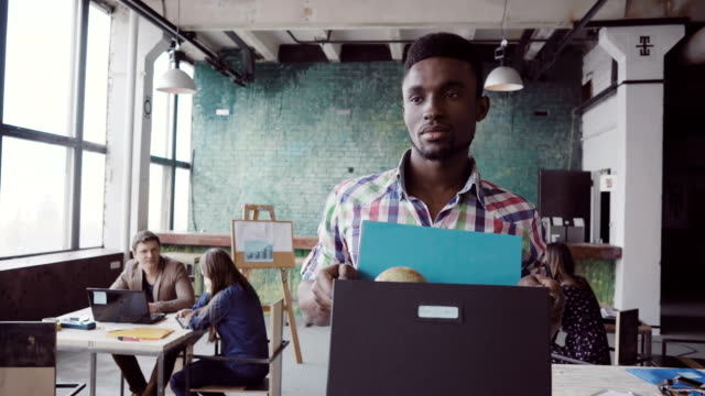 Young african man get fired from work at start-up. Male walks through the office, carrying box with personal belongings