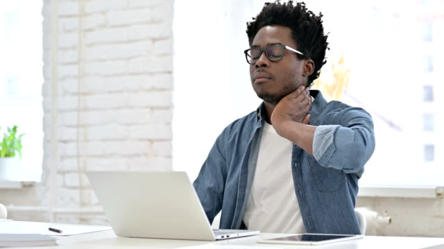 Young African Man having Neck Pain on Laptop