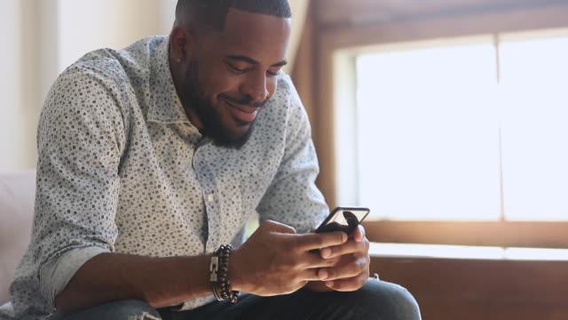 stockvideo's en b-roll-footage met jonge afrikaanse man het houden van smartphone texting bericht zittend thuis - daten
