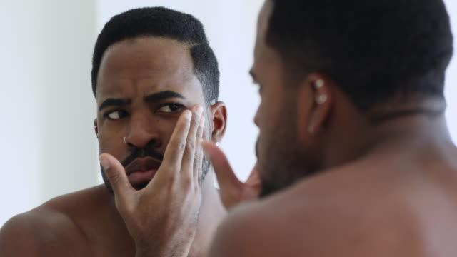 젊은 아프리카 남자 찾고 에 거울 데 얼굴 피부 문제 - 짜증 스톡 비디오 및 b-롤 화면