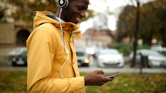 Young African man using phone Portrait of young African man relaxing and enjoying autumn in the public park,using phone headphones stock videos & royalty-free footage