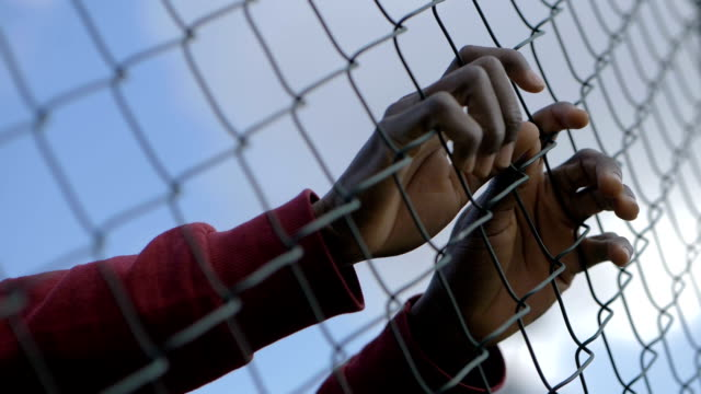 young african man's hands shaking prison net. Migration,illegality