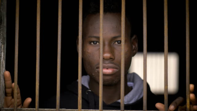 young african migrant behind bars. illegal migration,africa,prison - fuggitivo video stock e b–roll