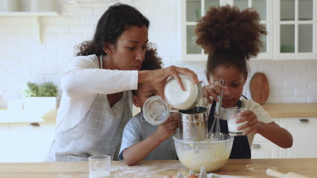 Young african mom housewife preparing dough with little daughter son