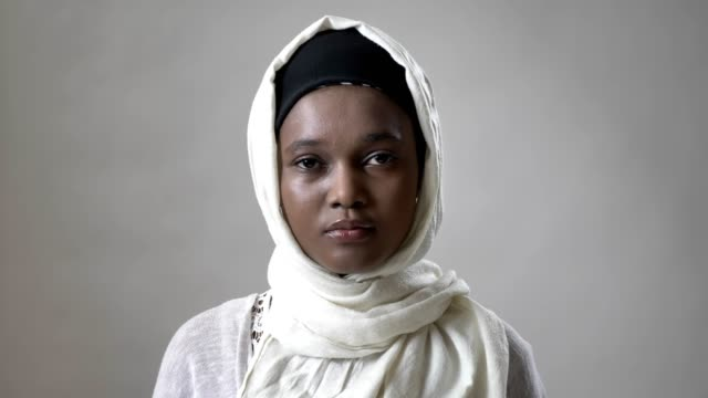 young african muslim girl in hijab is watching at camera, religioun concept, grey background - традиционная одежда стоковые видео и кадры b-roll