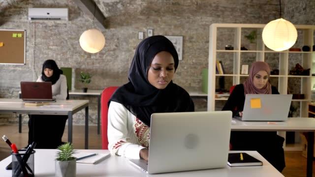 年輕非洲穆斯林婦女在頭巾打字膝上型電腦和咳嗽, 三美麗的穆斯林女性在現代辦公室工作 - 亞洲中部 個影片檔及 b 捲影像