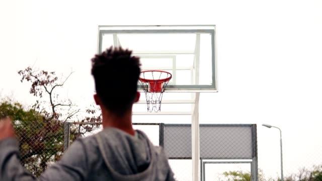 stockvideo's en b-roll-footage met jonge afrikaanse speler springen en gooien van de bal in een basketbal hoepel, de bal raakt de ring en de scores. de man draait zich om en kijkt in de camera. tikje schot - kampioenschap