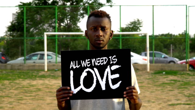 Young African Protestor is holding cardboard ''ALL WE NEED IS LOVE''