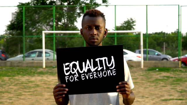 Young African Protestor is holding cardboard ''EQUALITY FOR EVERYONE''