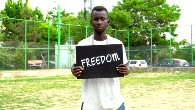 Young African Protestor is holding cardboard ''FREEDOM''