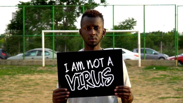 unga afrikanska protestor håller kartong ''jag är inte virus'' - etnicitet bildbanksvideor och videomaterial från bakom kulisserna